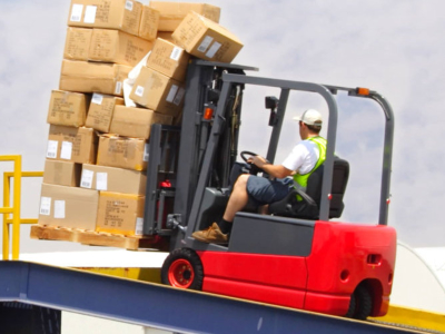 man using forklift to board packages on truck